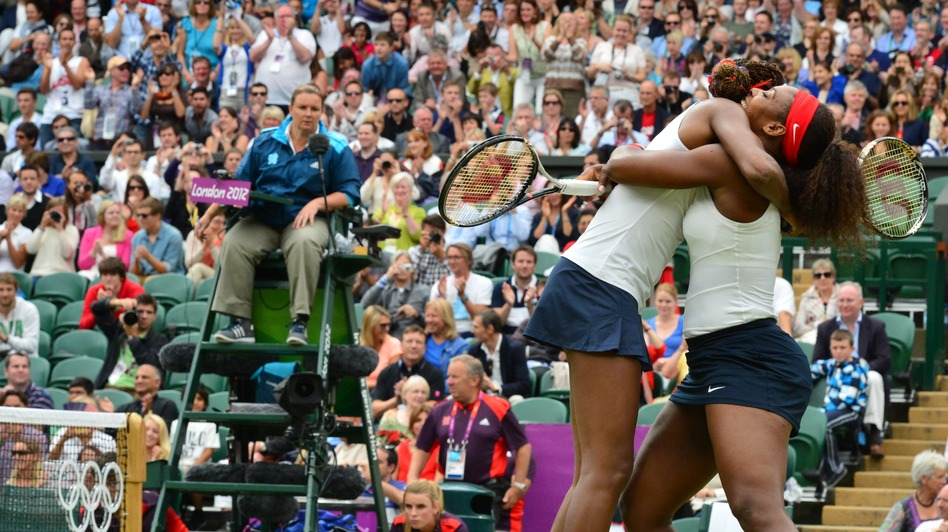 Venus (left) and Serena Williams celebrate after winning the women's doubles gold medal match today. (AFP/Getty Images)
