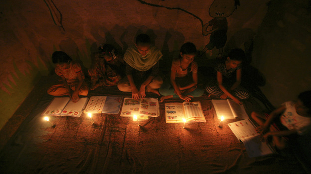 Muslim girls study by candlelight inside a religious school in Noida, near New Delhi, on July 31. The collapse of three regional power grids last week caused a massive power outage that blacked out more than half of India. (Reuters /Landov)