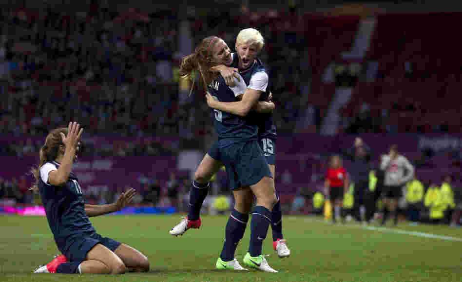 United States' Megan Rapinoe, right, celebrates with teammate Alex Morgan as Tobin Heath slides in on her knees after scoring against Canada during their semifinal women's soccer match at the 2012 London Summer Olympics, Monday.