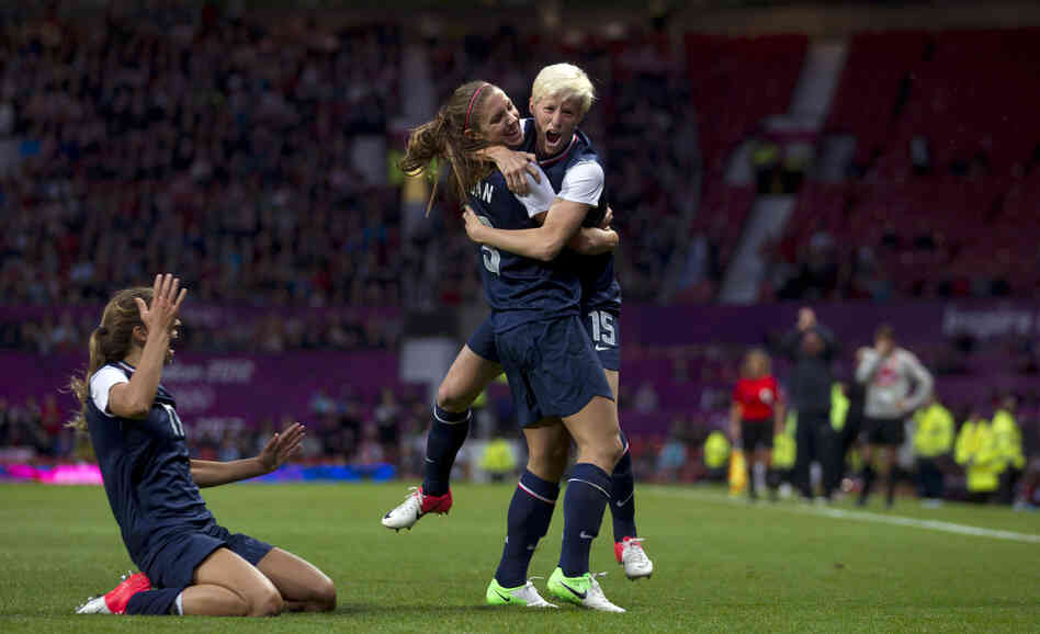 United States' Megan Rapinoe, right, celebrates with teammate Alex Morgan as Tobin Heath slides in on her kn