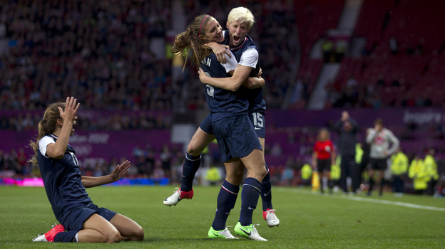United States' Megan Rapinoe, right, celebrates with teammate Alex Morgan as Tobin Heath slides in on her knees after scoring against Canada during their semifinal women's soccer match at the 2012 London Summer Olympics, Monday. (AP)