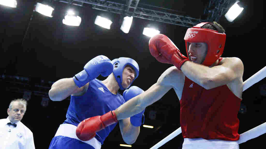 Siarhei Karneyeu of Belarus (in blue) landed most of the punches in the third round of his bout with Teymur Mammadov of Azerbaijan, who wasn't penalized for holding.