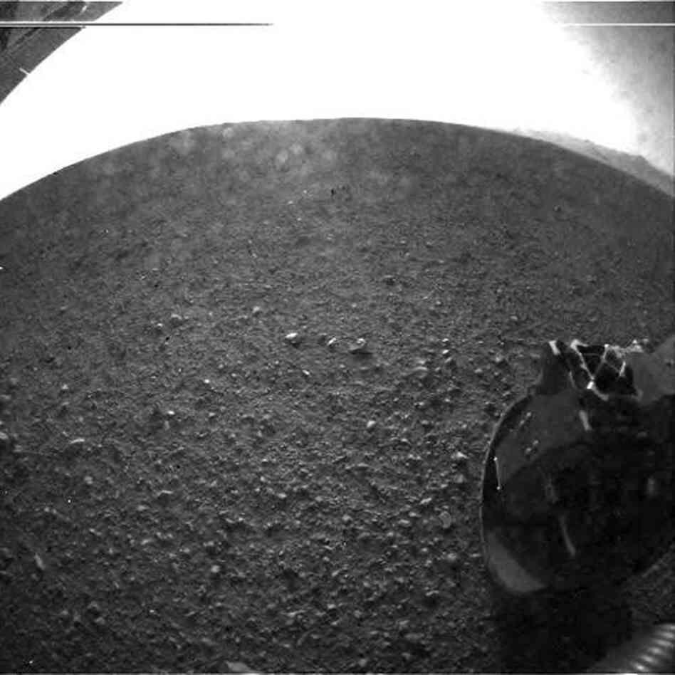 "This is one of the first images taken by NASA's Curiosity rover, which landed on Mars early Monday. It was taken through a wide-angle lens on the left ""eye"" of a stereo pair of Hazard-Avoidance cameras. Larger color images from other cameras are expected later in the week when the rover's mast, carrying high-resolution cameras, is deployed."
