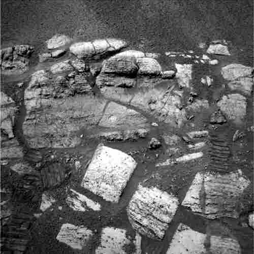 "Opportunity captures the layered rocks of the ""El Capitan"" area near the rover's landing site at Meridiani Planum, 2004. (Visible on two of the rocks are the holes drilled by the rover, which provided scientists with a window to this part of the red planet's water-soaked past.)"