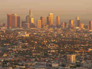 The Los Angeles downtown skyline gleams at sunset with a golden glow.