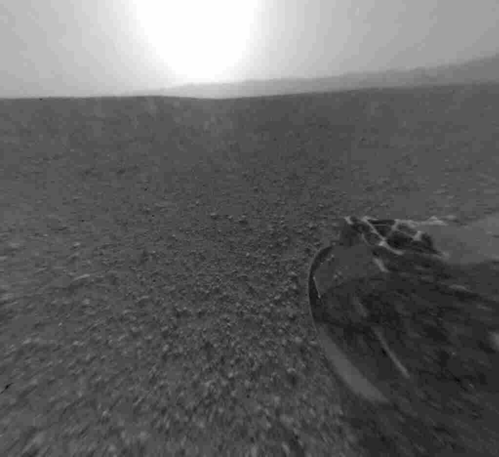 Part of the rim of Gale Crater, which is a feature the size of Connecticut and Rhode Island combined, stretches from the top middle to the top right of the image. One of the rover's wheels can be seen at bottom right.