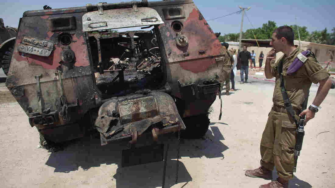 Militants drove two armored vehicles through a security fence into Israel from Egypt on Sunday, leaving 16 Egyptian soldiers dead and destroying two armored vehicles. An Israeli soldier inspects the wreckage of one of the Egyptian military trucks at a base in Kerem Shalom, Israel.