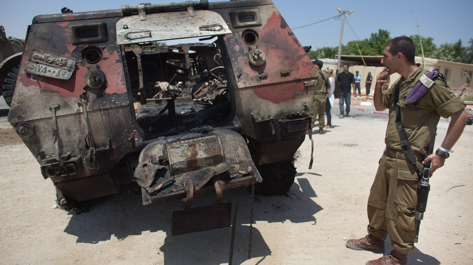 Militants drove two armored vehicles through a security fence into Israel from Egypt on Sunday, leaving 16 Egyptian soldiers dead and destroying two armored vehicles. An Israeli soldier inspects the wreckage of one of the Egyptian military trucks at a base in Kerem Shalom, Israel. (Getty Images)