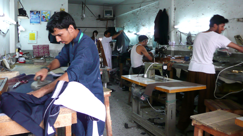 Workers in a tailor's workshop in Rawalpindi, Pakistan, use manual sewing machines, and sometimes stitch suits by hand, when the power goes out. Tailors are frantically trying to fill orders for new suits in time for the end of Ramadan. (Lauren Frayer for NPR)