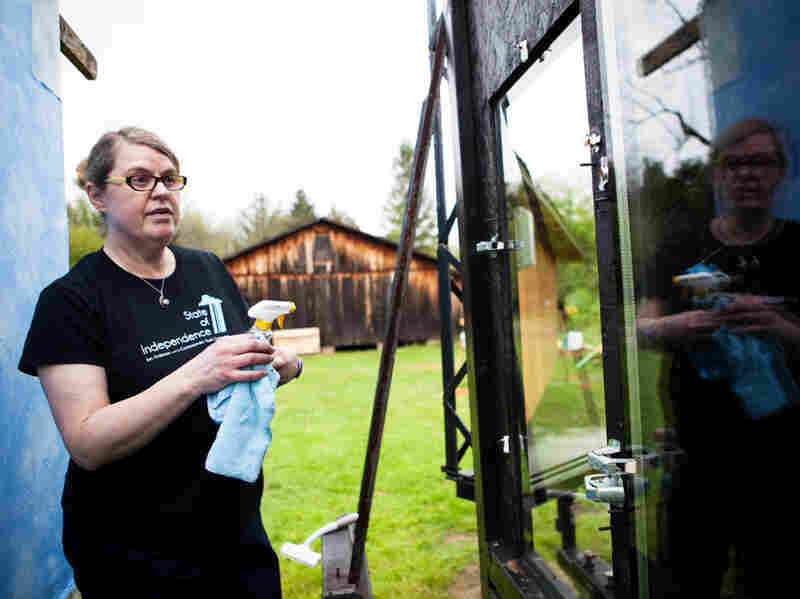 Christine Sheppard, an ornithologist with the American Bird Conservancy, cleans windows before conducting an experiment that will help determine which pane of glass is more bird friendly.