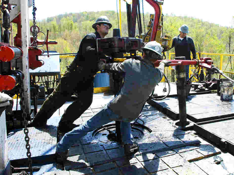Workers move a section of well casing into place at a Chesapeake Energy natural gas well site near Burlington, Pa., in 2010.