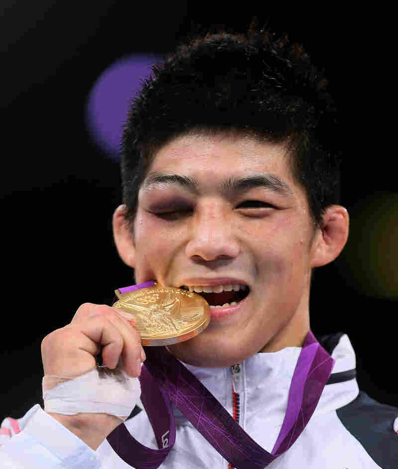 South Korea's Kim Hyeonwoo, winner of the gold medal in the 66-kilogram Greco-Roman Wrestling event, bites his medal as he poses on the podium. He won the final despite a badly swollen eye.
