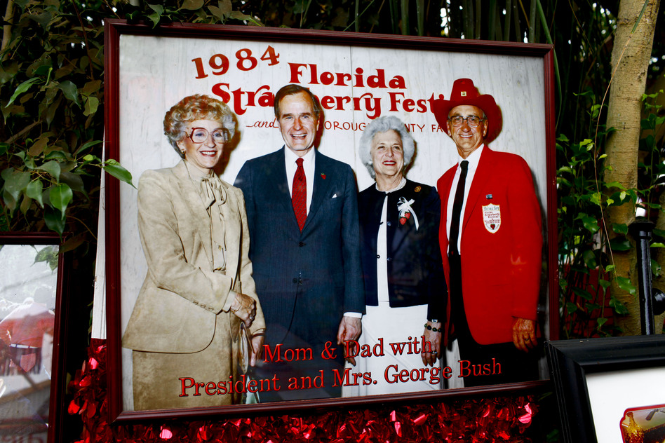 "The Meeks display a large photo of themselves posing with George and Barbara Bush in 1984. The market has become a ""must-visit"" destination for presidential candidates. (NPR)"