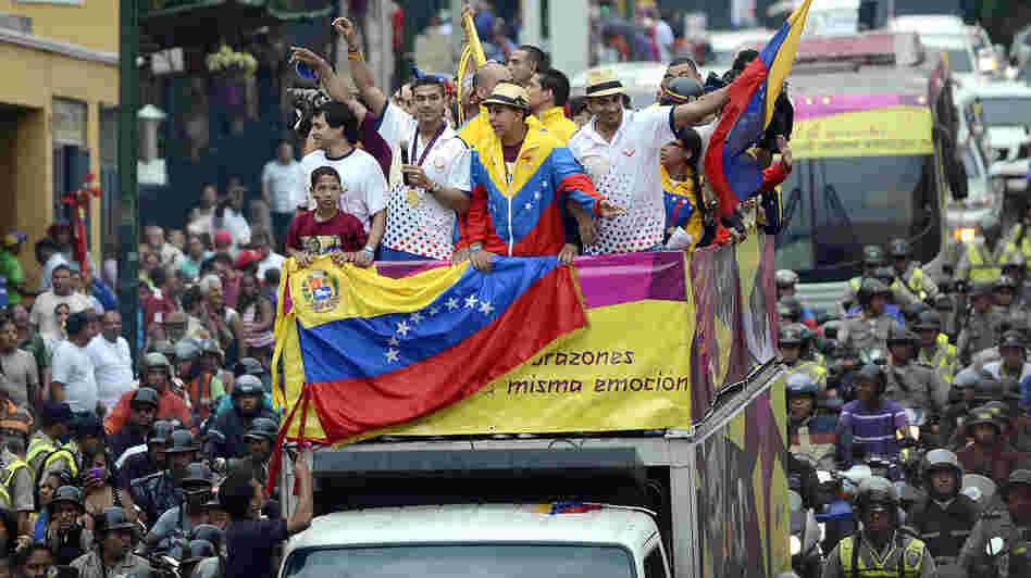 Venezuelan gold medal fencer Ruben Limardo (center) greets supporters after arriving in Caracas Monday. Limardo was received at the airport as a national hero, after winning the first gold medal for Venezuela in 44 years.