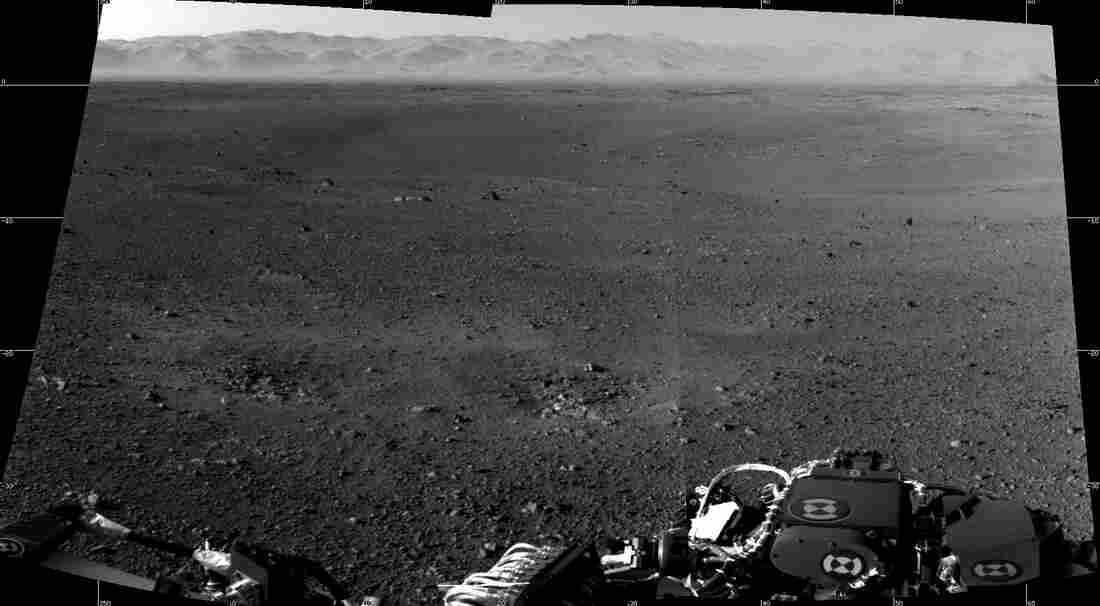 A photograph taken by NASA's Curiosity Rover on Mars. The rim of Gale Crater can be seen in the distance beyond the pebbly ground.