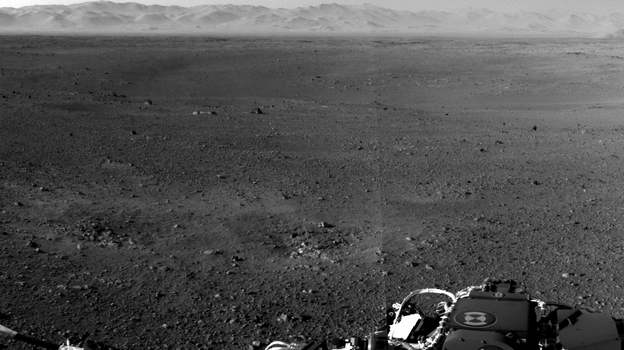 A photograph taken by NASA's Curiosity Rover on Mars. The rim of Gale Crater can be seen in the distance beyond the pebbly ground. (NASA/JPL-Caltech)