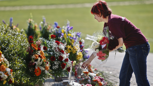 A visitor lays flowers on the Virginia Tech campus in Blacksburg, Va., on April 16, five years after a lone gunman killed 32 people. Many colleges formed threat assessment teams in the aftermath of the Virginia massacre. (AP)
