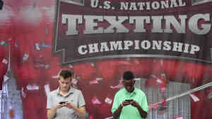 Austin Wierschke, left, of Rhinelander, Wis., and Kent Augustine, of Jamaica, N.Y., compete during the final round of the 2012 LG U.S. National Texting Championship on Wednesday, in New York. Wierschke won the championship for the second time in a row.
