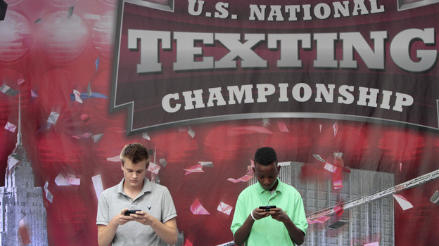 Austin Wierschke, left, of Rhinelander, Wis., and Kent Augustine, of Jamaica, N.Y., compete during the final round of the 2012 LG U.S. National Texting Championship on Wednesday, in New York. Wierschke won the championship for the second time in a row. (AP)