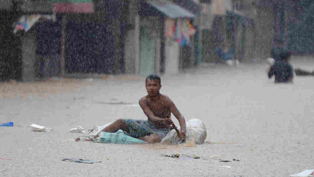 A man paddled an improvised raft along a flooded street in suburban Manila earlier today.