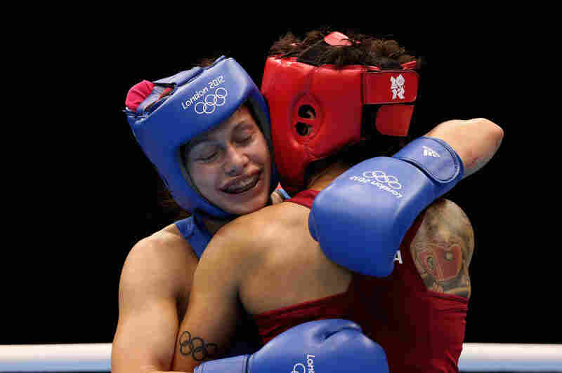 Sofya Ochigava (in blue) of Russia hugs Adriana Araujo of Brazil after their bout during the Women's Light Boxing semifinals on Day 12 of the London Olympic Games. Ochigava won the bout.