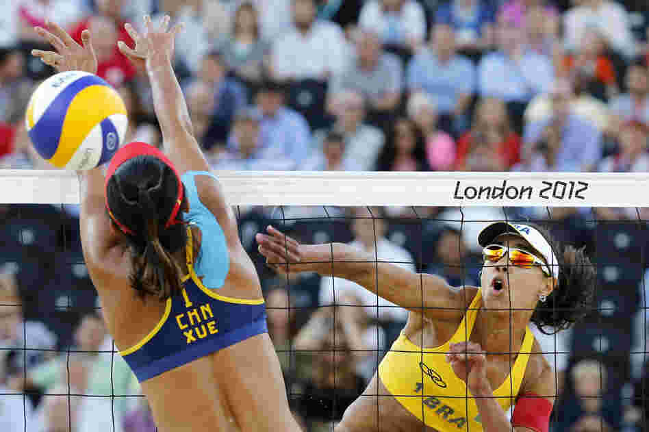 China's Xue Chen (left) blocks a spike by Brazil's Juliana Silva in their women's beach volleyball bronze medal match. Brazil won 2-1.