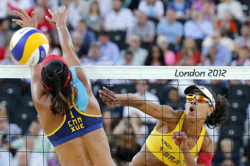 China's Xue Chen (left) blocks a spike by Brazil's Juliana Silva in their women's beach volleyball bronze medal match. Brazil won 2-1.