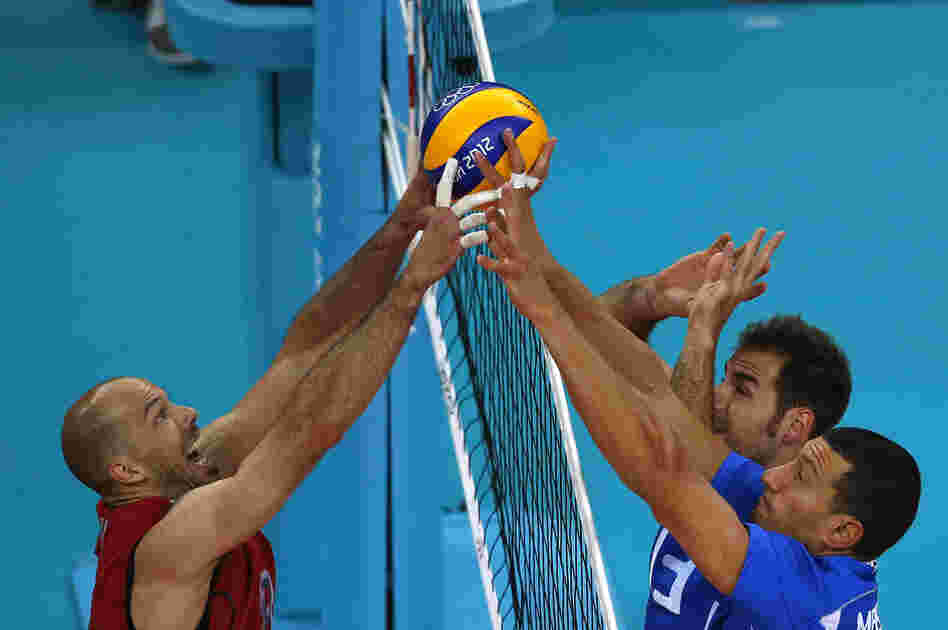 William Priddy (left) of the U.S. spikes the ball against Italy's Luigi Mastrangelo (right) and Dragan Travica during their men's quarterfinal volleyball match. Italy won the match 3-0.