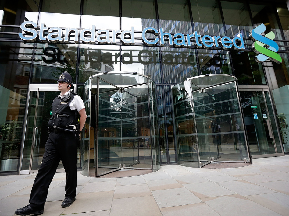 Police leave the Standard Chartered Bank's offices Tuesday in London. The bank has been accused of making billions of dollars' worth of transactions with the Iranian regime.