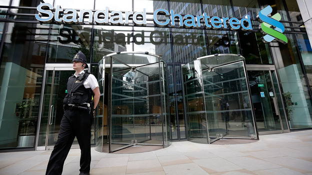 Police leave the Standard Chartered Bank's offices Tuesday in London. The bank has been accused of making billions of dollars' worth of transactions with the Iranian regime. (Getty Images)