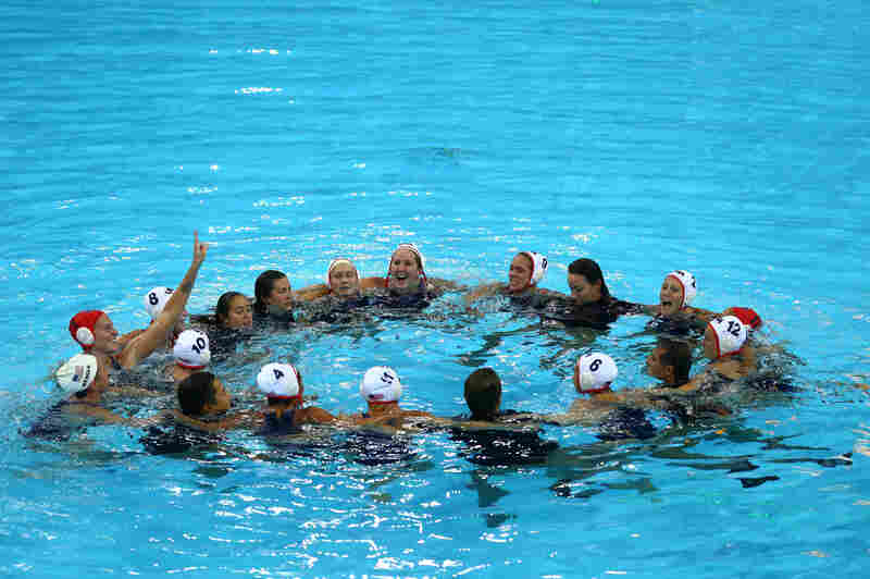 U.S. players and coaching staff celebrate winning gold in the women's water polo final against Spain.