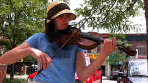 Alexis Dawdy plays her violin on the streets of Lansing, Mich.