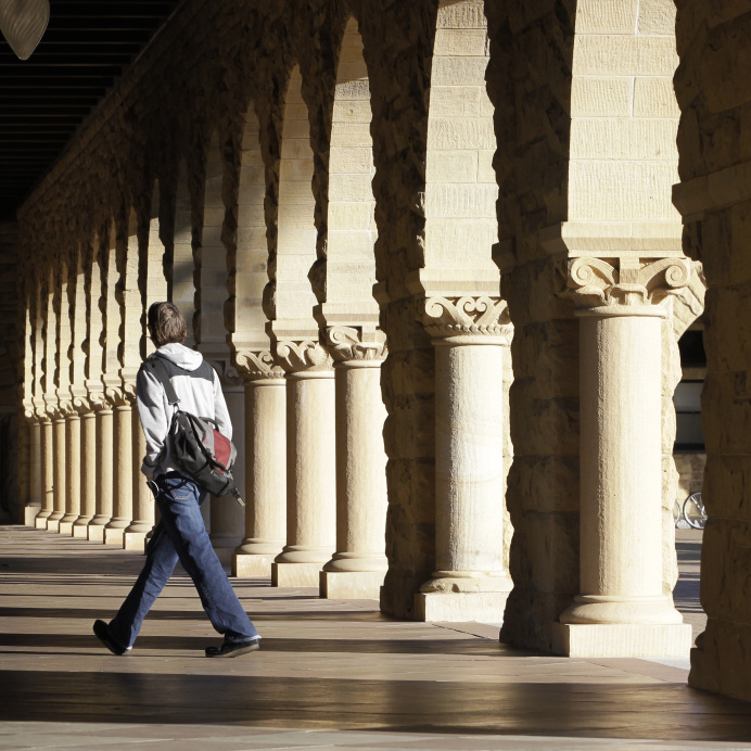 A Stanford University student walks through the campus in Palo Alto, Calif.
