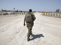 An Israeli soldier walks near the border between Israel and Egypt at the Kerem Shalom border crossing on Wednesday.