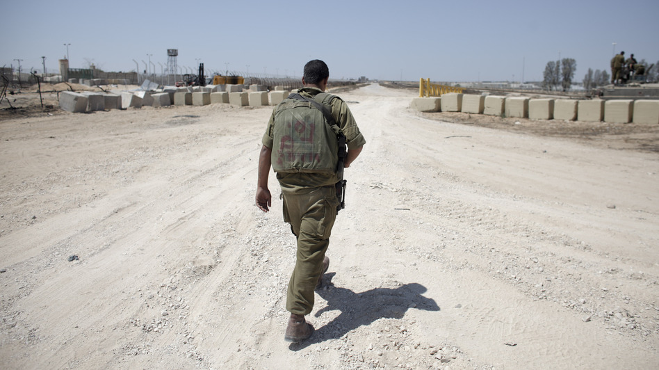 An Israeli soldier walks near the border between Israel and Egypt at the Kerem Shalom border crossing on Wednesday. (Tara Todras-Whitehill for NPR)