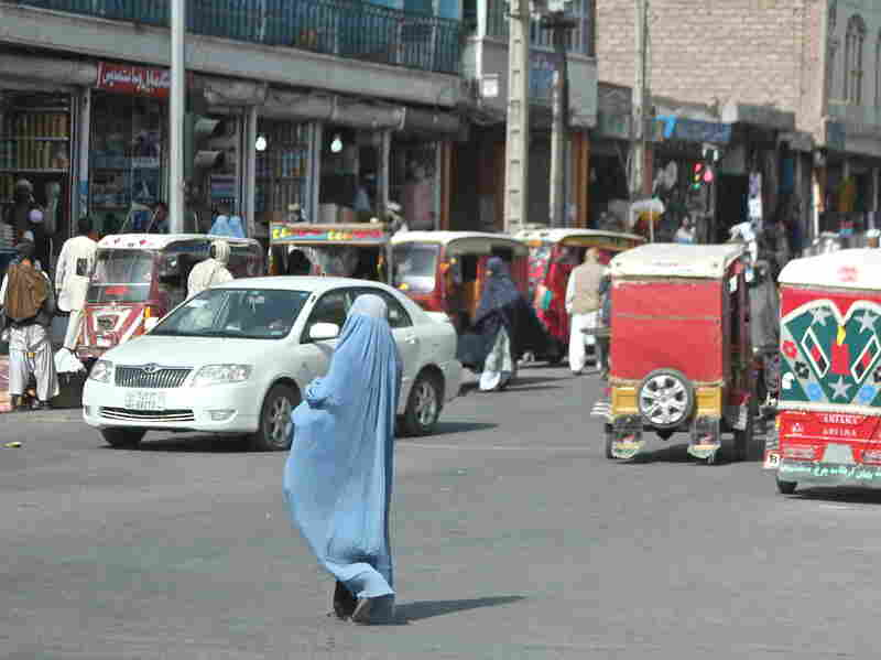 A woman crosses the street in Herat, Afghanistan. Burqa-clad women stand out on the streets in Afghanistan — both because of their bright blue burqas, and because there are far fewer women in public than men.