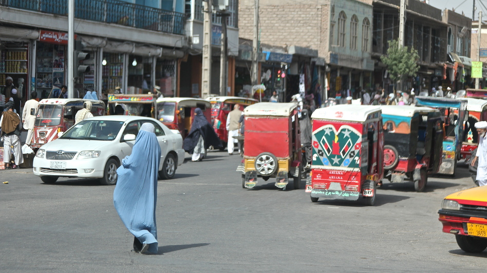 A woman crosses the street in Herat, Afghanistan. Burqa-clad women stand out on the streets in Afghanistan — both because of their bright blue burqas, and because there are far fewer women in public than men. (NPR)