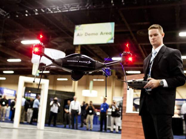 Brian Bills, a flight operations analyst for Lockheed Martin, demonstrates the Procerus VTOL (vertical takeoff and landing) Flight System — a surveillance drone for commercial, civil and military customers — at the Association of Unmanned Vehicle Systems International conference in Las Vegas. (Watch a demo video.)