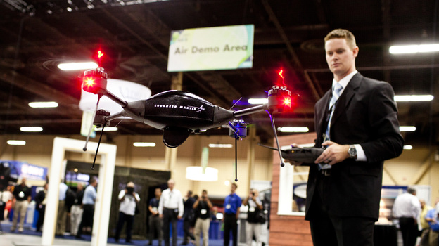 Brian Bills, a flight operations analyst for Lockheed Martin, demonstrates the Procerus VTOL (vertical takeoff and landing) Flight System — a surveillance drone for commercial, civil and military customers — at the Association of Unmanned Vehicle Systems International conference in Las Vegas. (Watch a demo video.) (NPR)