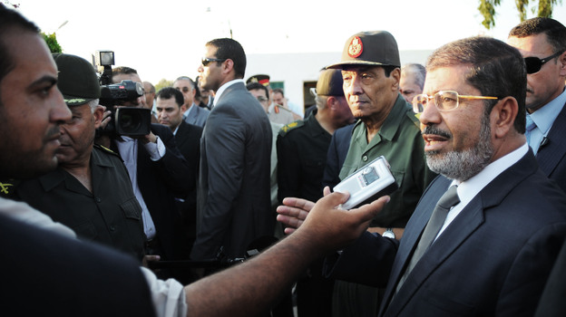 Egyptian President Mohammed Morsi (right) speaks to the media on Aug. 6 in El Arish, Egypt. He has already been engaging with the public more regularly than his predecessor. (AP)