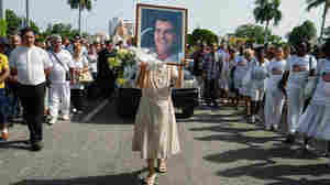 Oswaldo Paya, who challenged Cuba's communist regime for decades, died in a car crash on July 22. A Spanish man who was driving Paya has been charged with the equivalent of vehicular manslaughter. Here, a nun holds a portrait of Paya during his funeral in Havana.
