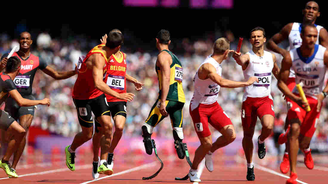 Anticipation: Oscar Pistorius of South Africa waits for the baton in the team 4x400m relay at London's Olympic Stadium. His teammate fell in the race, but officials deemed he had been interfered with. South Africa will run in the final.