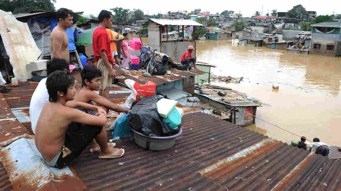 From a rooftop in a Manila suburb today, residents watched water flow through flooded streets.