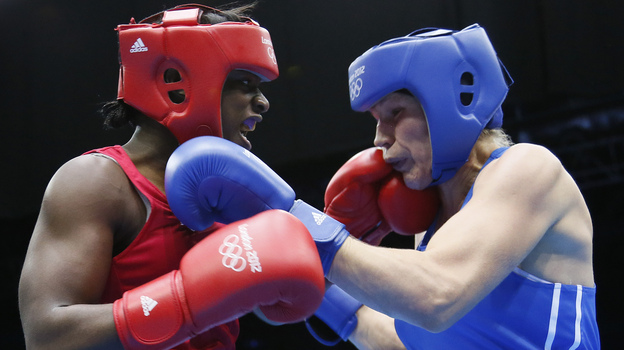 U.S. boxer Claressa Shields (left) lands a punch on Nadezda Torlopova of Russia during the women's boxing middleweight final at the ExCel Arena in London. Shields, 17, won the first-ever gold medal in the event. (AFP/Getty Images)