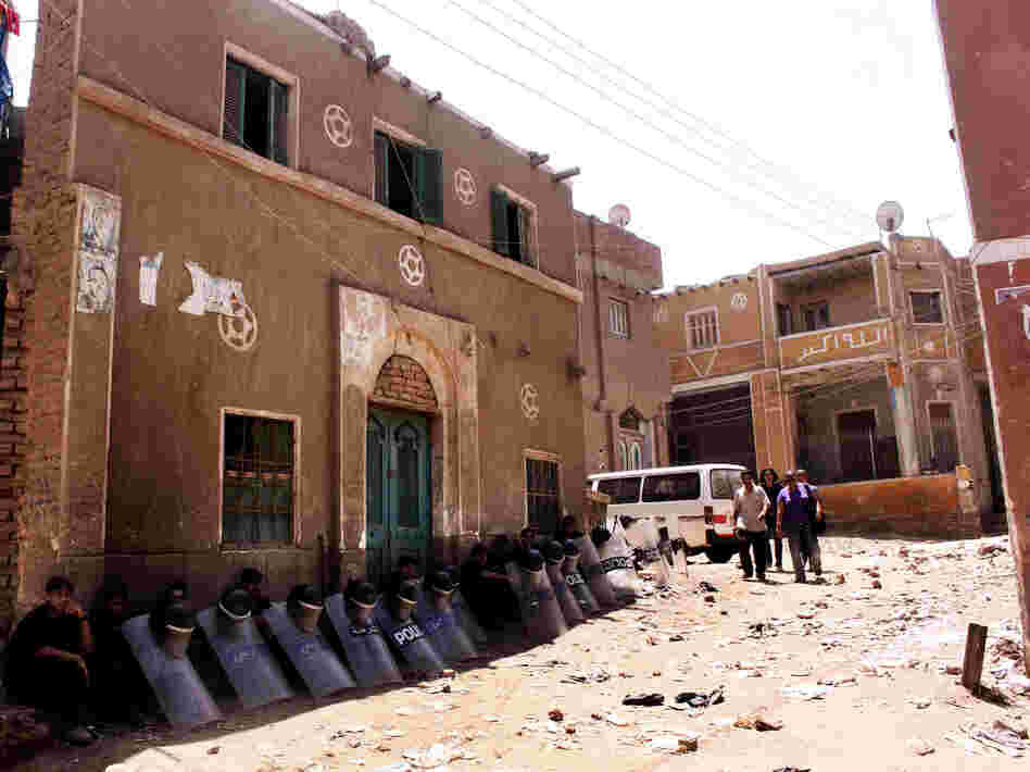 Egyptian riot police sit in the shade by damaged buildings as people walk through debris from the aftermath of clashes on Aug. 1 between Christians and Muslims in Dahshour, on the outskirts of Cairo. The violence was sparked by a dispute between a Muslim and Christian over laundered clothing.