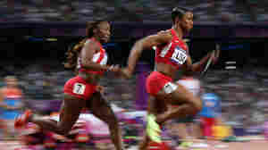 Carmelita Jeter of the United States receives the relay baton fom Bianca Knight of the United States on their way to winning gold in the Women's 4 x 100m Relay Final Friday.