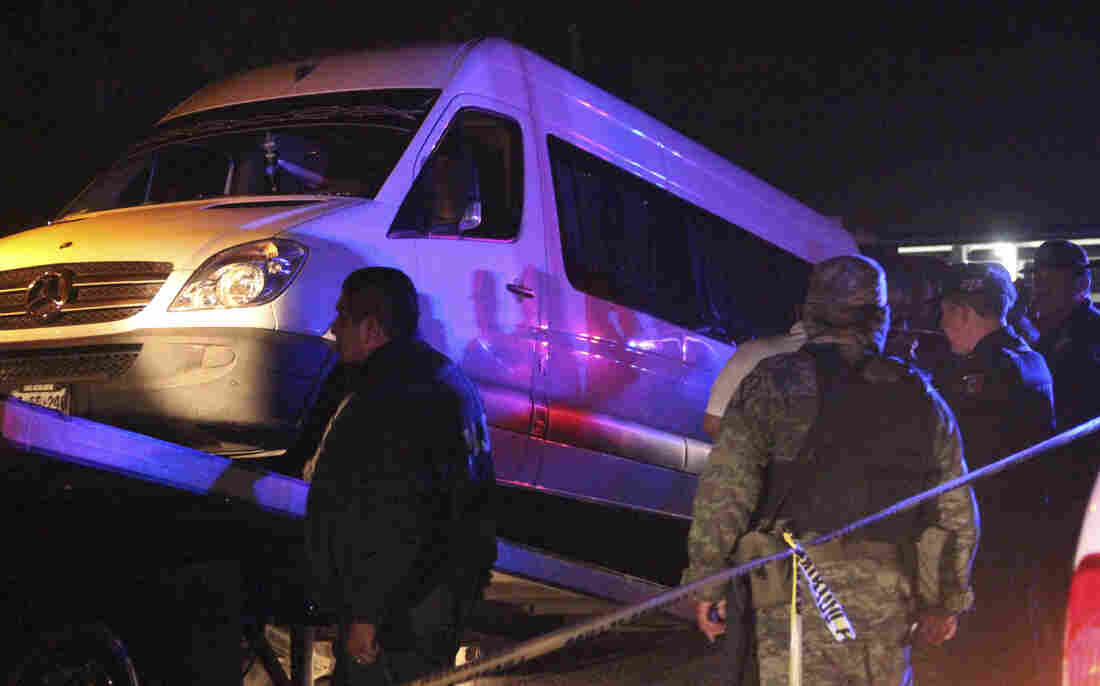 Police officers and soldiers stand around a white van containing the dead bodies of several man while it is being hauled onto a tow truck in San Luis Potosi on Thursday.