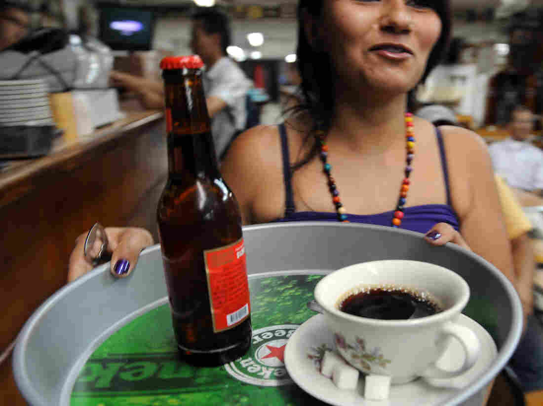 A waitress delivers a coffee and beer in Medellin, Colombia, in this 2010 file photo. Both drinks can trigger acid reflux.