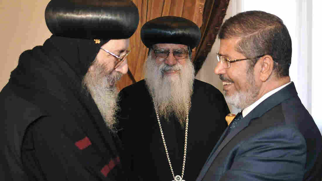 Then-President-elect Mohammed Morsi greets Coptic Bishop Bishoy (left) as Bishop Bakhomious looks on, at the presidential palace in Cairo in June, in this photo released by Egypt's official news agency. The election of Morsi, of the Muslim Brotherhood, has unnerved many Christians, who make up about 10 percent of Egypt's population.