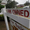 "A ""bank owned"" sign in front of a home in Miami last October."